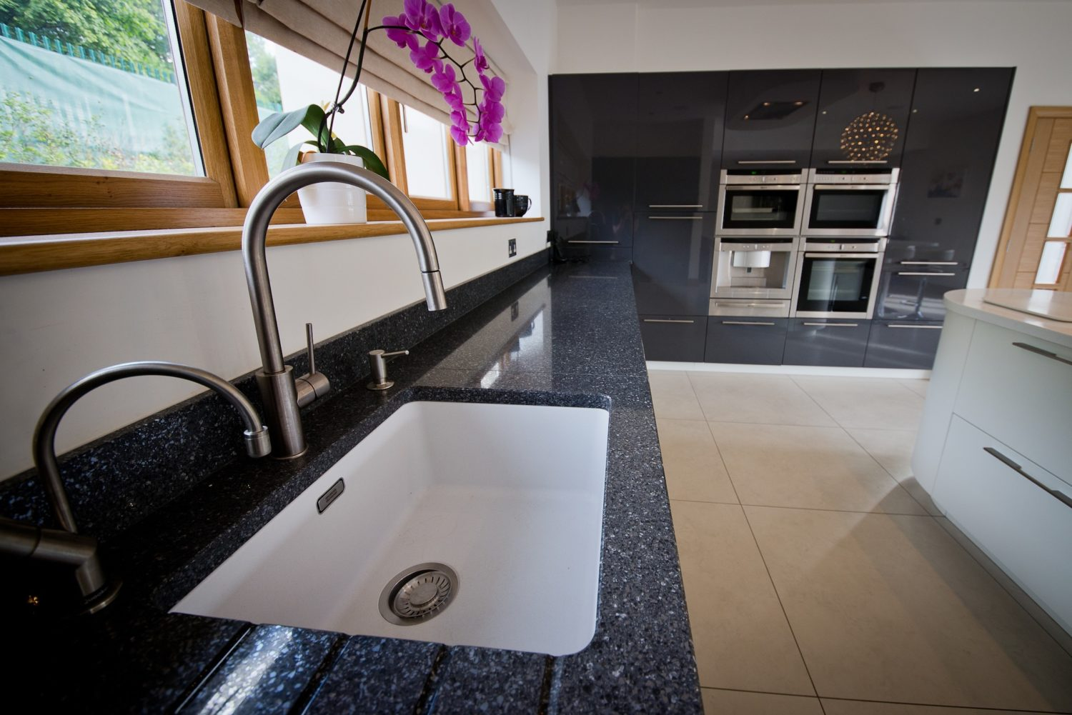 Organic quirky shaped white island with high gloss black units